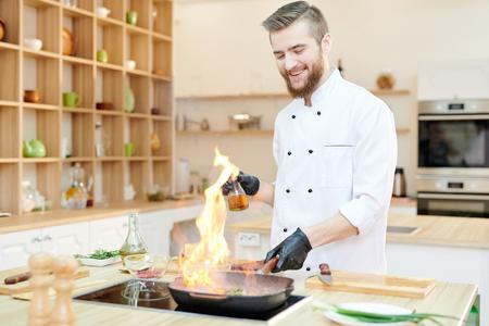 Fröhlicher Koch, der Flambe kocht