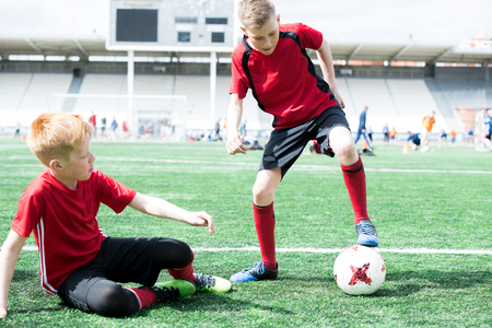 Children Playing Football in Stadium Stock Photo