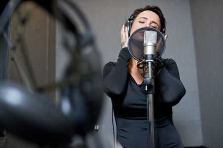 Beautiful woman singing in studio