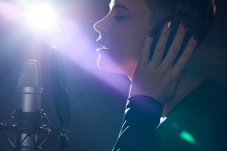 Emotive girl singing with microphone Stock Photo