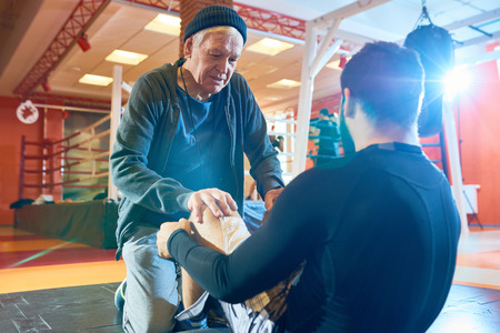 Elderly trainer working out with man Stock Photo