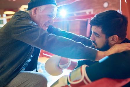 Professional trainer inspiring boxer
