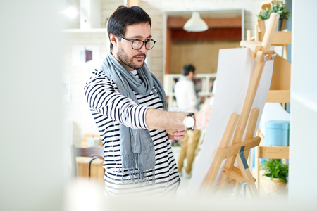 Trendy man painting on easel Stockfoto