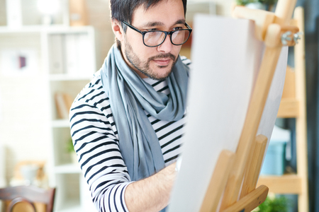 Bearded designer making art on paper