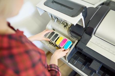 Mujer de cultivo poniendo tinta en impresora