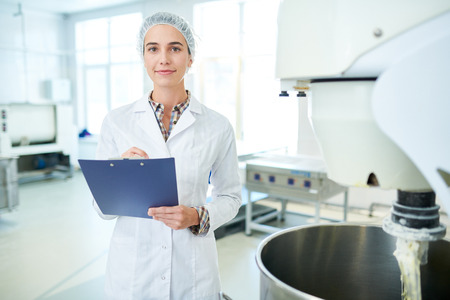 Confectionery factory worker standing with clipboard