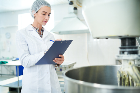 Confectionery factory worker taking notes Standard-Bild