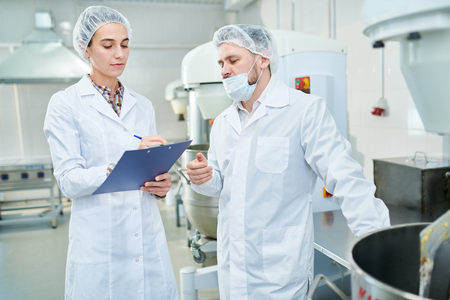 Professional confectioners discussing in factory