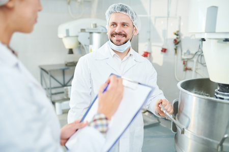 Smiling confectionery factory worker and colleague taking notes 스톡 콘텐츠