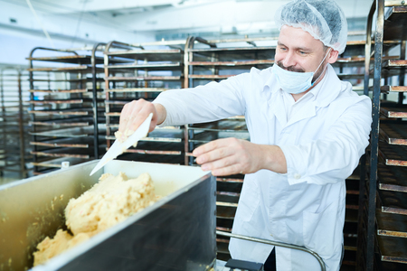 Confectioner mixing dough in factory Imagens