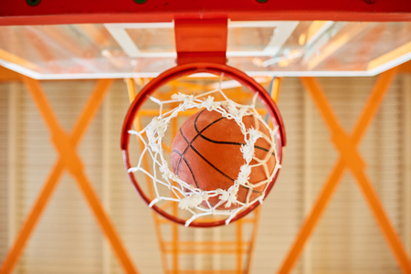 Ball falling through basketball basket 写真素材