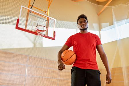 Black sportsman on basketball court Stock Photo