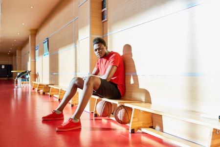 Black basketball player resting on bench