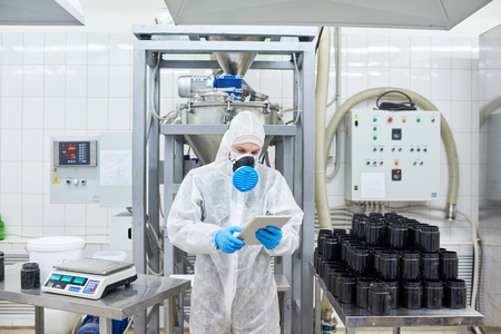 Factory worker standing and using tablet