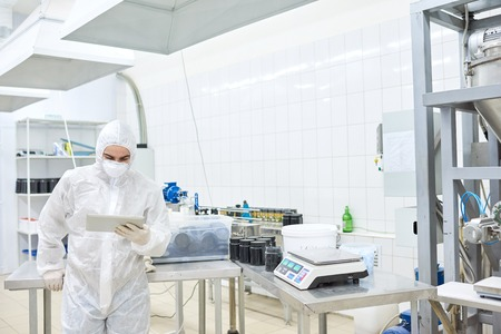 Factory employee in protective clothing using tablet