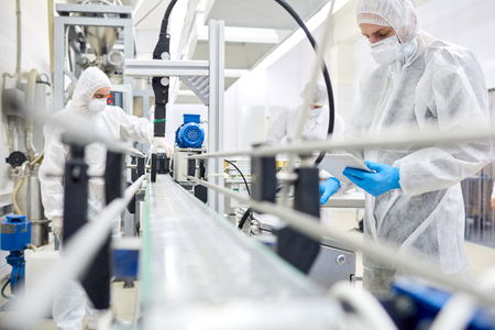 Pracownicy fabryki pracujący przy przenośniku taśmowym