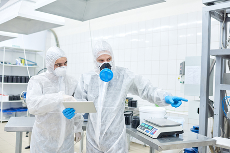 Factory worker using tablet and pointing to colleague