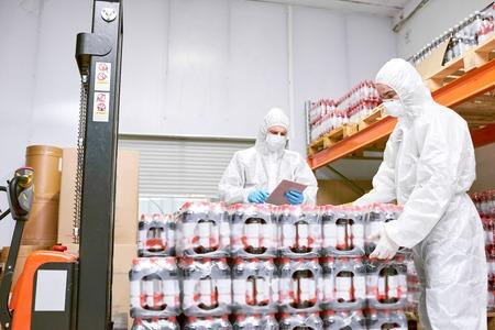 Factory workers unloading packs of bottles 写真素材