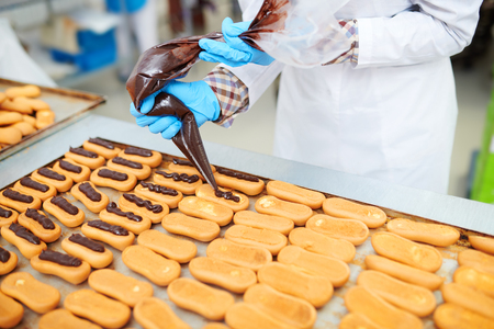 Confectioner decorating pastry using icing bag