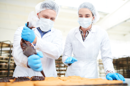 Confectioners pouring chocolate cream from pastry bag