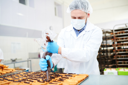 Confectionery factory worker decorating pastry using icing bag Foto de archivo - 103428110