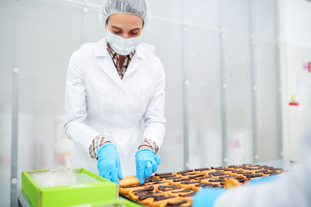 Confectionery factory worker packing ready pastry Foto de archivo - 103428113