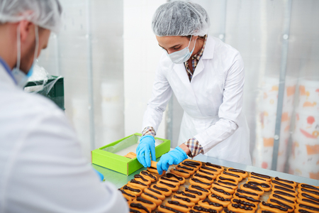 Confectionery factory employees packing ready pastry Foto de archivo - 103428115