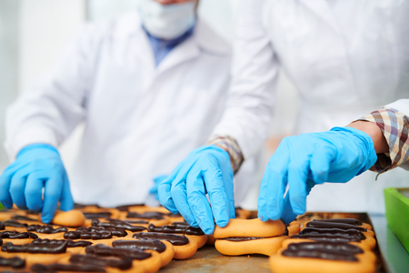Confectionery factory employees making pastry with chocolate filling