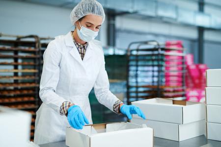 Trabajador de una fábrica de confitería preparando el paquete