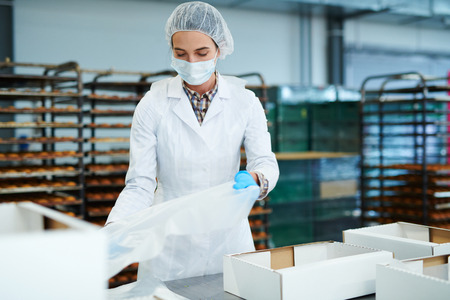 Confectionery factory worker preparing empty boxes