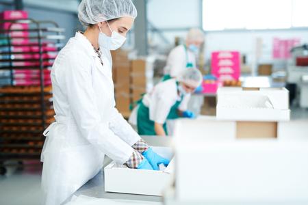 Empleado de la fábrica de confitería poniendo pergamino en caja