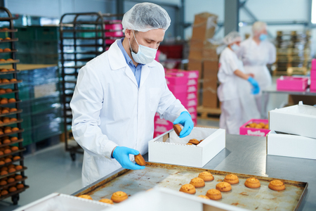 Confectionery factory worker packing pastry into box Archivio Fotografico
