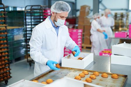 Ouvrier d'usine de confiserie, emballage de pâtisserie dans une boîte