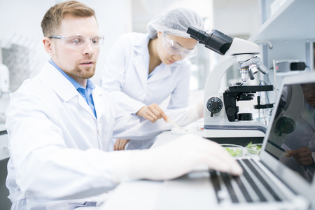 Scientist typing results of microscope research
