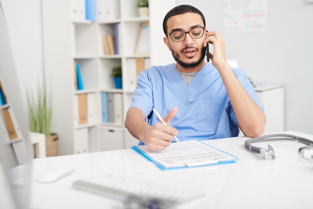 Middle-Eastern Doctor Speaking by Phone in Office Stockfoto