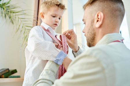 Padre cariñoso vestirse a su hijo Foto de archivo - 104021483