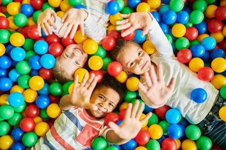 Drie kinderen spelen in de ballenbak