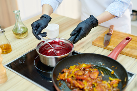 High angle close up of unrecognizable female chef stirring sauce while cooking dishes in modern restaurant kitchen