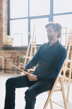 Mature Artist Sketching in Studio Stock Photo