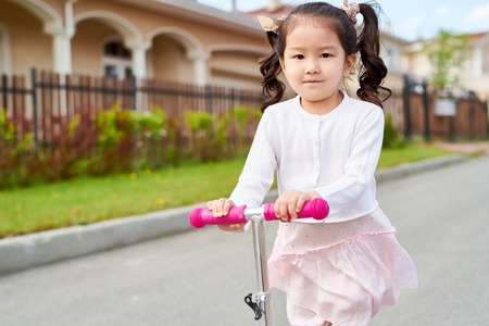 Little Asian Girl Riding Scooter