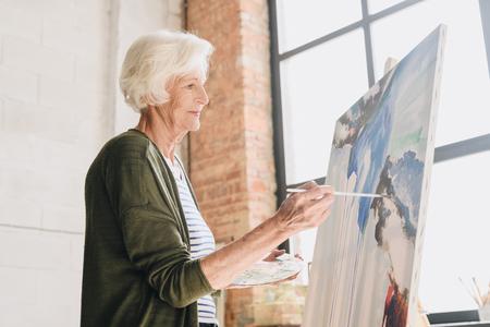 Talentierte ältere Frau, die im Kunststudio malt