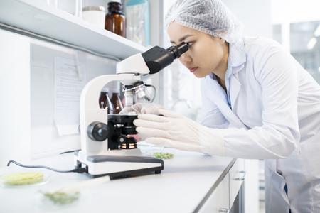 Scienziato femminile asiatico facendo uso del microscopio