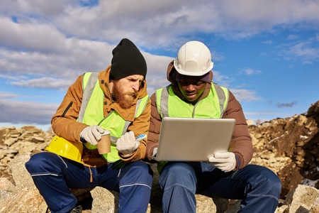 Workers Using Laptop on Excavation Site Stock Photo