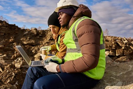 Miners Using Laptop on Excavation Site