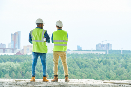 Anonymous construction engineers looking at city Stock Photo