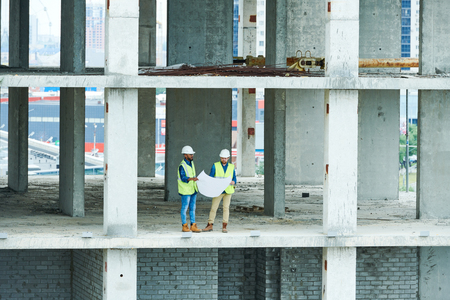 Construction engineers with draft in concrete building 写真素材