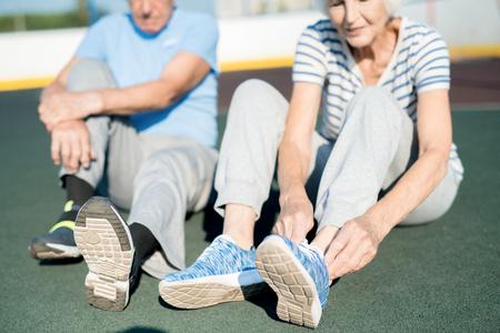 Senior Couple Tying Shoes on Track