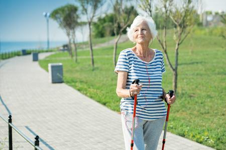 Ältere Frau Nordic Walking