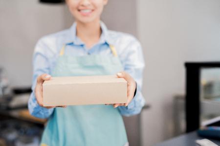 Mujer sosteniendo una caja con comida para llevar
