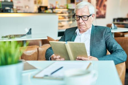 Senior Man Reading Book in Cafe